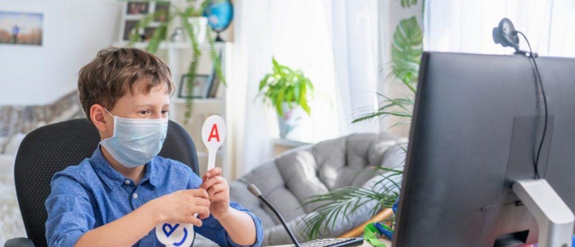 boy in face mask using computer, doing homework during coronavirus quarantine