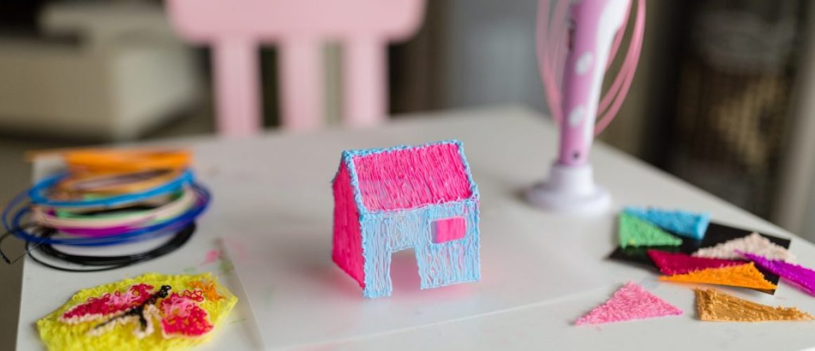 Cute little girl makes a plastic house, draws parts with a 3D pen. STEM and STEAM education. Development, modeling, education, design with hot plastic. Modern technologies. DIY.