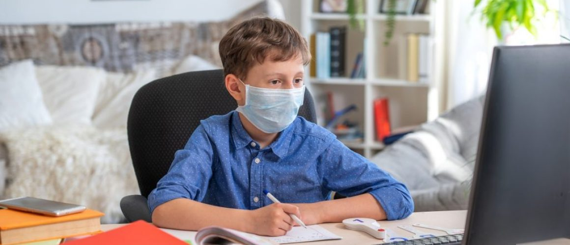 boy in face mask using computer, doing homework during coronavirus quarantine