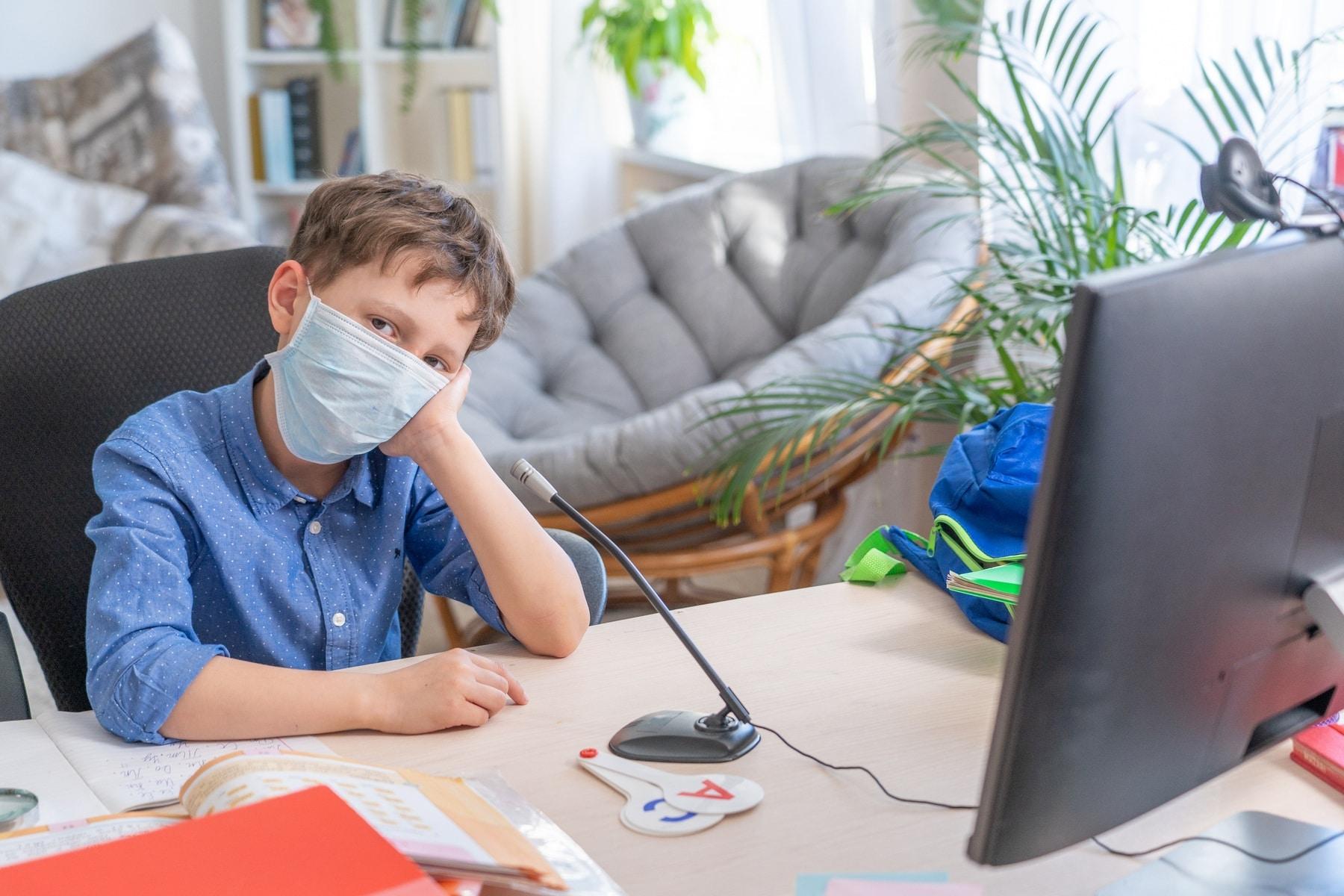 Sad boy in face mask using computer doing homework during coronavirus quarantine