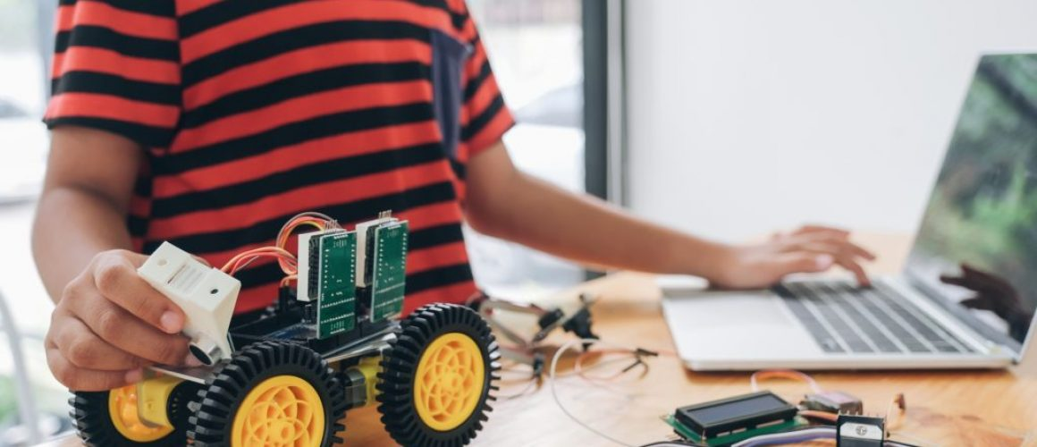 Boy with tablet pc computer programming electric toys and buildi