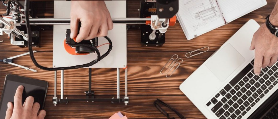 Three men are working on creating a 3d printer.