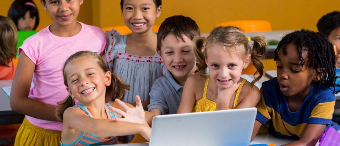 Portrait of smiling multi ethnic children using laptop in clasroom