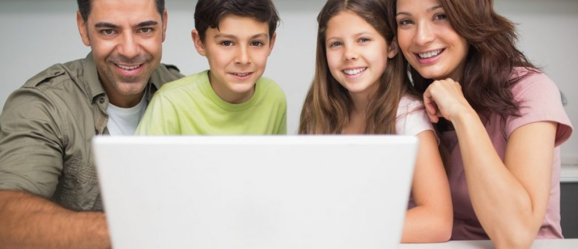 Portrait of a smiling couple with young kids using laptop at home